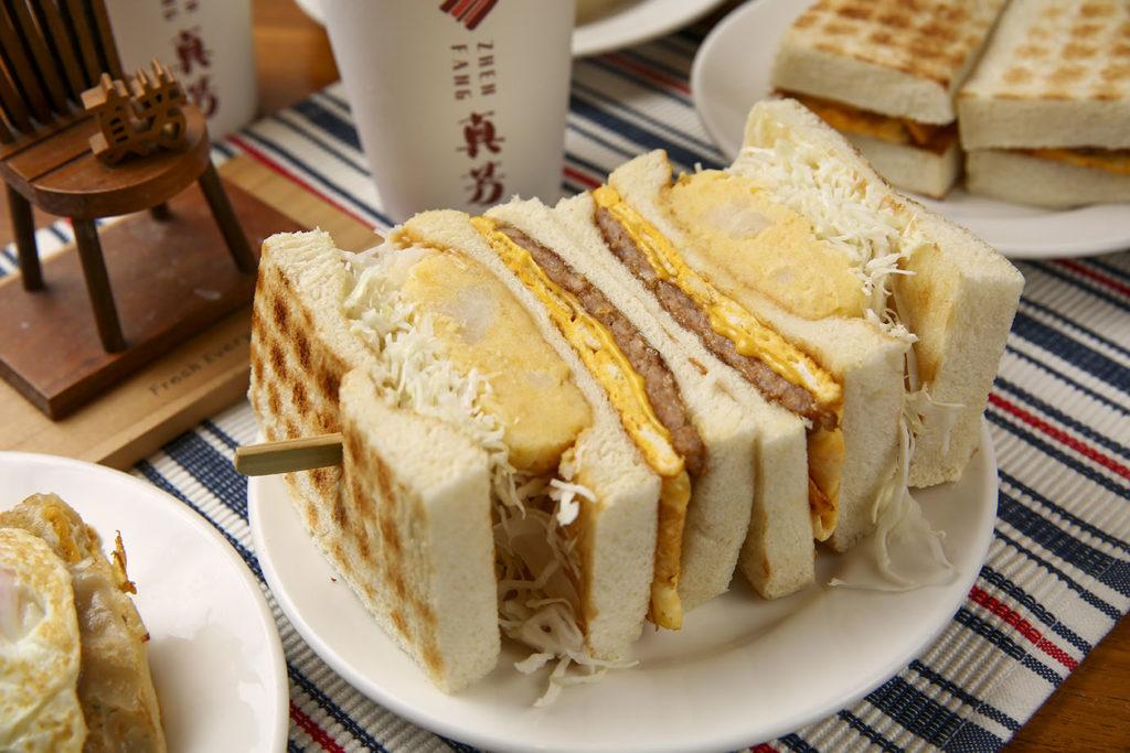 份量極大的真芳三明治,內有自製美乃滋、金瓜馬鈴薯沙拉、手打胛心肉排、高麗菜絲、特調花生醬、切達起司與牧場雞蛋,飽足感與一餐該有的營養,這份三明治全都為你顧到了。(圖.蔡暉宏攝)