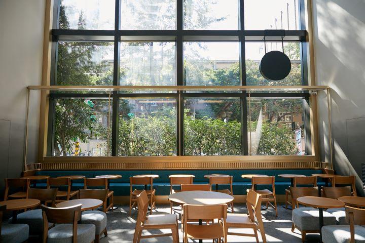 沿著牆面窗框的ㄇ字型樑柱,以細緻的銅色烤漆條收邊,帶領顧客享受室內挑高空間。(圖.星巴克 提供)