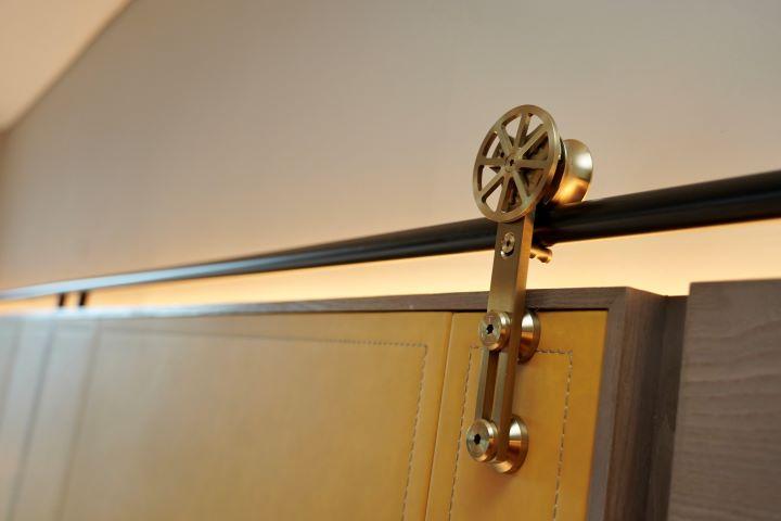 客房內的床頭板也運用精緻的五金材質呈現膠捲軸心。(圖.林玉偉 拍攝)