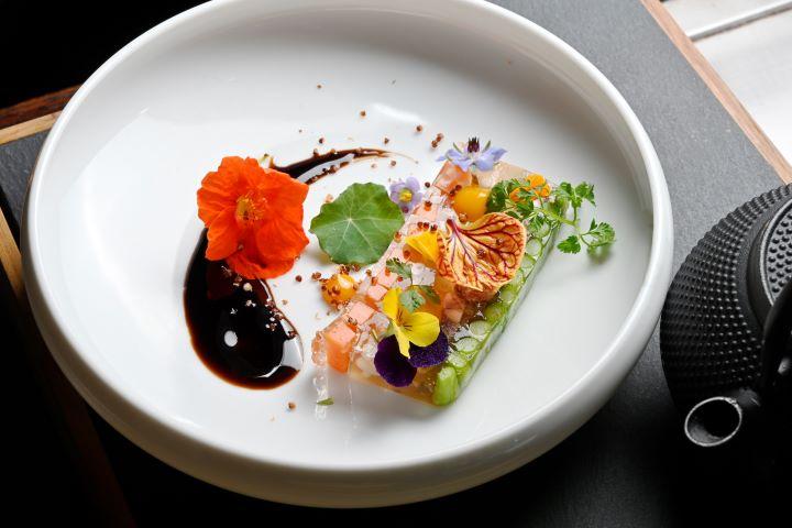 擁有日料背景的鄭安宏主廚,首道前菜「春蔬琥珀肉凍」充滿著日料雅致的擺盤美學。(圖.陳思明 攝影)