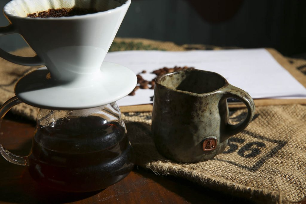 祕魯日曬慢乾處理法咖啡風味豐足,一旁的「手捏虎字杯」是Alex請老師純手工製作,用來喝咖啡喝水都會特別溫潤。(圖.蔡暉宏攝)