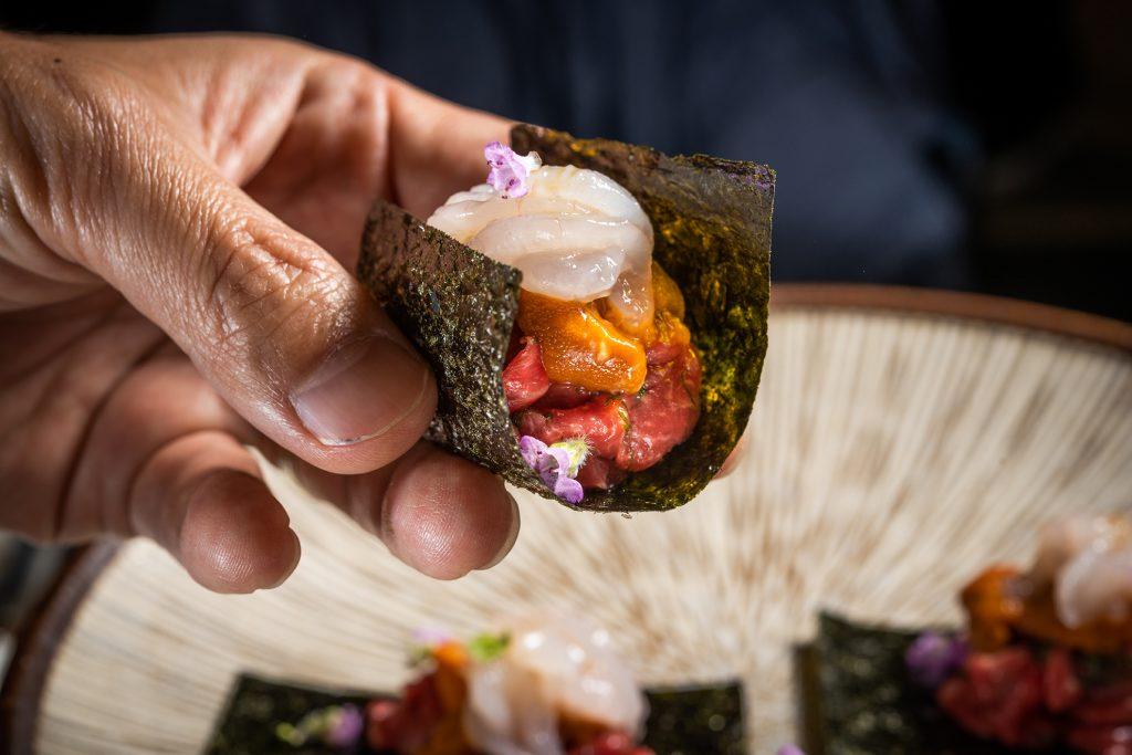 極上生牛肉,類似日式割烹料理,以佐賀海苔包著北海道海膽、富山灣白蝦與生牛肉絲,一口吃下,滿嘴好滋味。 (圖.徐嘉駒攝)